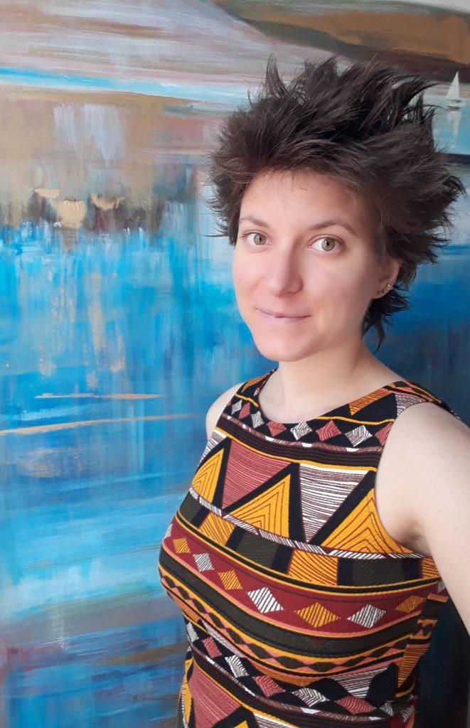 agathe photo souriante de présentation, robe colorée, toile de peinture bleue, masseuse tantrique et éducatrice sexo